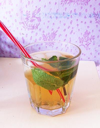 Eisteezubereitung mit Pfirsichtee und Minze im Glas mit Strohhalm