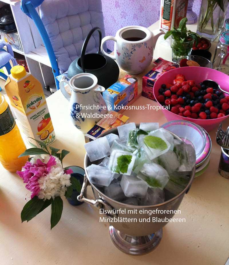 Eisteezubereitung mit eingefrorenen Minzblättern und Blaubeeren in Eiswürfel